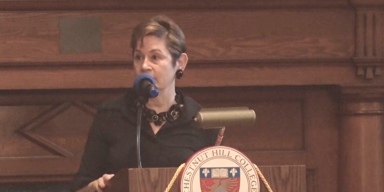 PMC's President & CEO, Maida Milone, speaking behind a podium at Chesnut Hill College